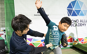 子供にピッチングフォームを教えるトレーナー